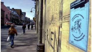 Person walking past a sign in Quebec City