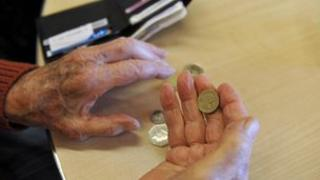 An elderly person with coins