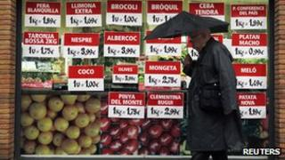 Man walking past grocery shop in Spain