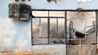 A burned out birdcage hangs from a wall outside a house in Ecatepec in Mexico on 7 May 2013