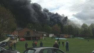Thick black smoke over the cricket pitch.