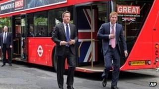 David Cameron and Prince Harry beside double decker bus made by Wrightbus in Ballymena