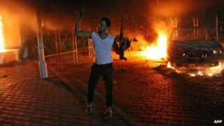 An armed man waves his rifle as buildings and cars are engulfed in flames after being set on fire inside the US consulate compound in Benghazi late on 11 September 2012