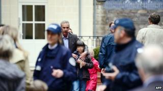 Parents pick up their children as policemen stand guard at the entrance of the nursery school in Paris (16 May 2013)