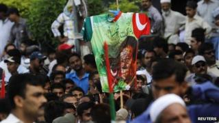 "A supporter of Pakistan""s Muttahida Quami Movement (MQM) holds a dirt-stained T-shirt with an image of Imran Khan, leader of the Pakistan Tehreek-e-Insaf (PTI), during a protest against him in Karachi May 20, 2013."