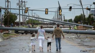A family walks a street blocked by fallen utility poles in Moore, Oklahoma, on 21 May 2013