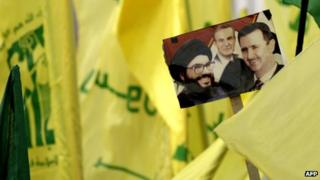 Hezbollah supporters (not seen) hold a picture of Hezbollah leader Hassan Nasrallah (L), Syrian President Bashar al-Assad (R) and his late father president Hafez al-Assad (C) in the southern town of Bint Jbeil on 22 September 2012