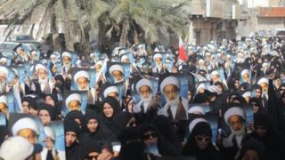 Protesters carrying images of Sheikh Isa Qassim walk in Diraz 24 May 2013