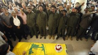 Supporters of Hezbollah and relatives of Saleh Ahmed Sabagh, a Hezbollah member, gesture during his funeral