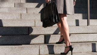 Woman with briefcase climbing stairs