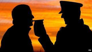 Silhouette of person being breath tested by a police officer