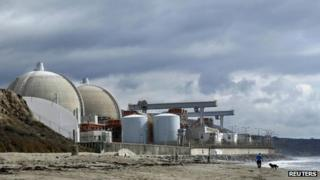 A man walks his dog next to the damaged San Onofre power plant located next to San Onofre State Park in California 8 November 2012
