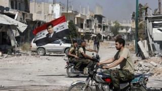 Forces loyal to President Bashar al-Assad carry the national flag as they ride on motorcycles in Qusair, after the Syrian army took control from rebel fighters, June 5, 2013.