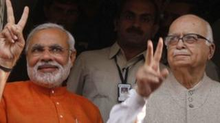 In this Dec. 17, 2012 file photo, Gujarat Chief Minister Narendra Modi, left, flashes a victory sign as he sees off Bharatiya Janata Party (BJP) senior leader Lal Krishna Advani, right