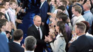 Russian President Vladimir Putin greets supporters as he arrives at the founding congress of a movement called the All-Russia Popular Front