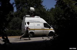 A man runs past a van of Greek public broadcaster ERT outside its headquarters in Athens, 17 June