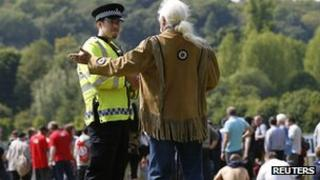 Policeman talks to a protester on the perimeter of the Bilderberg conference