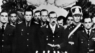 General Orlando Ramon Agosti (R) and Admiral Emilio Massera (L) stand as Lieutenant General Jorge Rafael Videla (C), President of Argentina, takes an oath as 38th president of the Argentine Republic, 29 March 1976, in Buenos Aires.