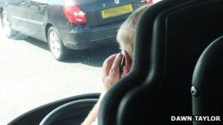 Photo taken of driver appearing to use mobile phone at the wheel