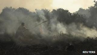 A resident tries to extinguish a fire burning on peatland in Pekanbaru of Riau province, 24 June 2013