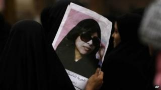 A Bahraini anti-government protester carries a picture of jailed opposition activist Zainab al-Khawaja