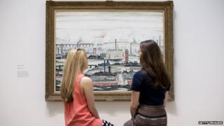 Museum employees pose for a picture in front of English artist Laurence Stephen Lowry's painting 'Industrial Landscape 1955' at the Lowry and the Painting of Modern Life exhibition at Tate Modern