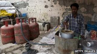 A roadside teashop owner makes tea next to LPG cylinders in New Delhi.