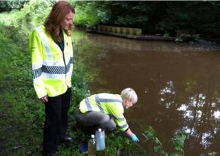 Environment Agency officials taking samples from a canal