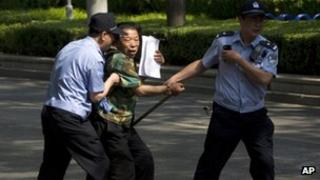 File photo: a petitioner trying to attract public attention is taken away by policemen in Beijing, China, 8 May 2012