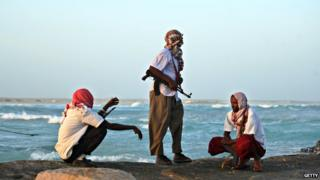 Armed pirates keep watch on the Somali coast in 2010