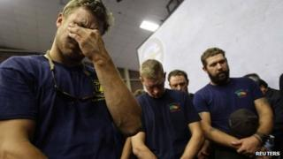 Hotshot firefighters mourn during a moment of silence for the 19 firefighters who perished battling a fast-moving wildland fire at a memorial service, in Prescott, Arizona 1 July 2013