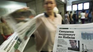 An employee distributes newspapers with a photograph of Edward Snowden seen on a page, at an underground walkway in central Moscow on 2 July 2013