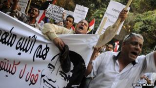 Egyptians protest outside US embassy in Cairo on 14 July 2012 as Secretary of State Hiilary Clinton visits the country