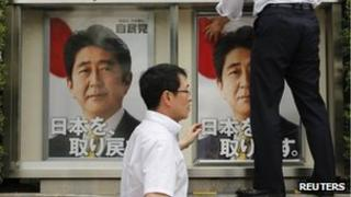 Staff members of Japan's ruling Liberal Democratic Party (LDP) put up posters of Japan's Prime Minister Shinzo Abe, who is also leader of the LDP, at the LDP headquarters in Tokyo, 4 July 2013