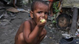 An Indian child eats rice in a slum in Guwahati in Assam on 4 July 2013