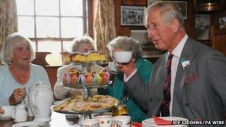 Prince Charles enjoys a cup of tea with members of the Tuesday Club during a visit to the Prince of Wales Inn, Bridgend