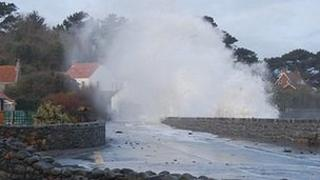 Waves crash over the sea wall at Perelle