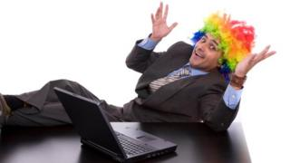 Man in clown wig writes on laptop