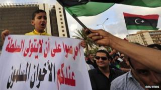 "A boy holds a sign that reads: ""Do not take power with you, Brotherhood"" as protesters wave the Libyan flag during a demonstration against the Muslim Brotherhood for interfering in local politics, in Benghazi, Libya, 10 May 2013"