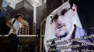 Man walking by a poster of Edward Snowden in Hong Kong