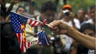 A woman burns US flags during a protest in support of Bolivian President Evo Morales in front of the US embassy in Mexico City, on 4 July