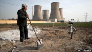 Man looking towards power station chimney stacks in Zingtai