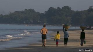 Tourist jogs alongside strolling Burmese on Ngapali beach, Burma, 28 November 2012