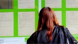 Young woman looking a job vacancies board