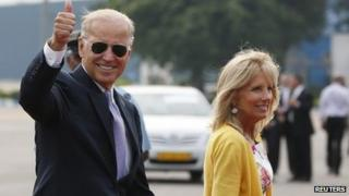 U.S. Vice President Joe Biden gestures as he and his wife Jill (R) arrive at the airport in New Delhi July 22, 2013