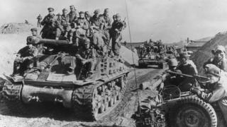 British soldiers travelling on a tank in Korea