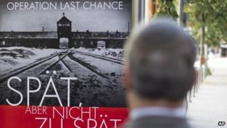 "The Simon Wiesenthal Center's Efraim Zuroff stands in front of a poster reading ""Operation last chance - late but not too late"" on 23 July 2013"