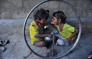 In this photograph taken on October 3, 2011, Indian children eat food at their temporary shelter on the side of the road in Hyderabad.