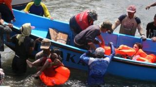 Rescuers assist survivors arriving on fishing boat at the wharf of Cidaun, West Java on July 24, 2013 after an Australia-bound boat carrying asylum-seekers sank off the Indonesian coast