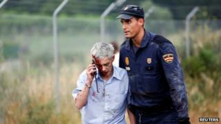 Train driver Francisco Jose Garzon Amo is helped by a policeman after a train crashed near Santiago de Compostela, 24 July 2013.